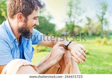 Man clicking on a screen of his smart watch sitting on a grass in a park.  - stock photo
