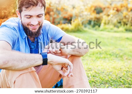 Man clicking on a screen of his smart watch sitting on a grass in a park - stock photo