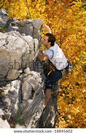 Man climbing a rock short before reaching the summit - stock photo