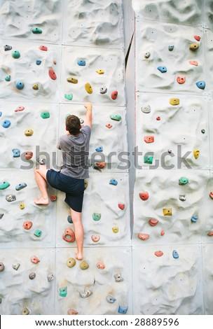 man climbing a wall - stock photo