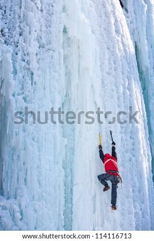 Man climbing frozen waterfall - stock photo