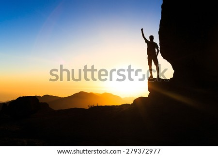 Man climbing hiking exploring accomplish silhouette in mountains, sunset and ocean. Male hiker with backpack on top of mountain looking at beautiful night landscape. - stock photo