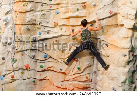 Man climbing on man-made cliff in the sport centre - stock photo
