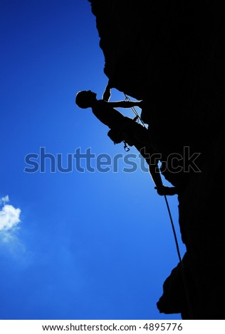 man climbing on the rock behind the sky - stock photo