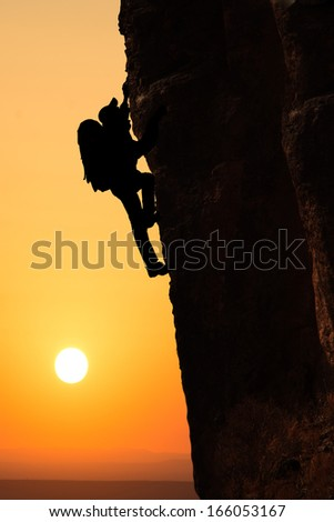 Man climbing on the rock on sunset background - stock photo