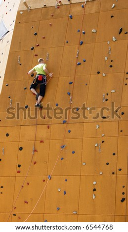 man climbing to the top of wall - stock photo