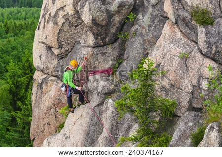 Man climbs a vertical wall of one of the rocks against forest - stock photo