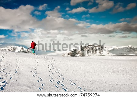Man climbs on a snow slope with skis in hand. Antarctica. - stock photo