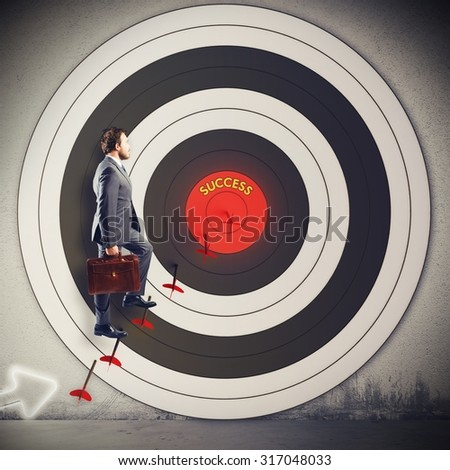 Man climbs on the arrow of target - stock photo