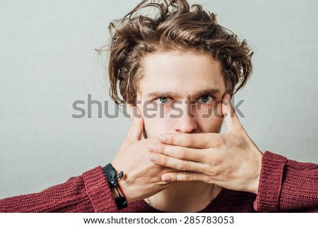 man closes the mouth with his hands - stock photo