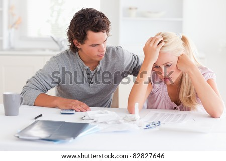 Man comforting his wife in their living room - stock photo