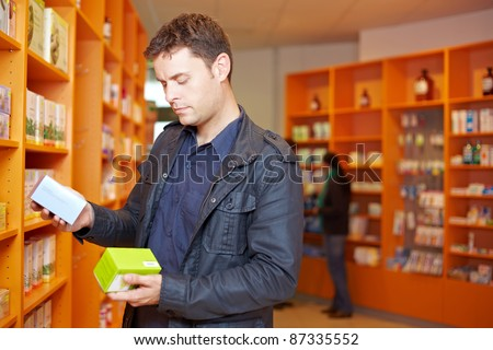 Man comparing two medical products in a pharmacy - stock photo