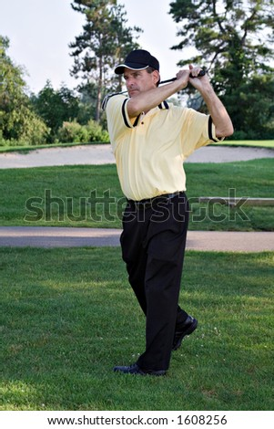 Man completes golf swing. - stock photo