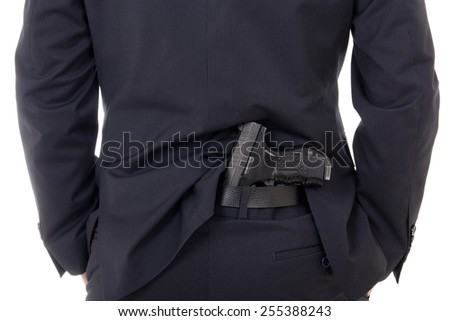 man concealing gun in pants behind his back isolated on white background - stock photo