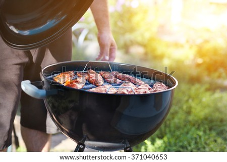 Man cooking fish fillets on the grill with flames in horizontal orientation - stock photo