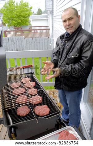 Man cooking hamburgers on a BBQ - stock photo