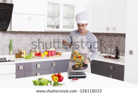 Man cooking in kitchen - stock photo