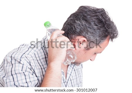Man cooling down with a bottle of cold water as summer heat or heatwave concept - stock photo