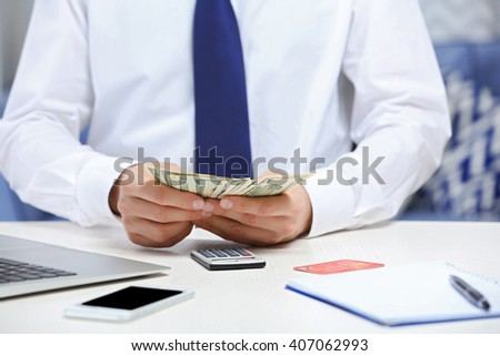 Man counting money and making calculations - stock photo