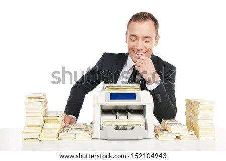 Man counting money. Cheerful young businessman counting money on the money counting machine while sitting at the table - stock photo