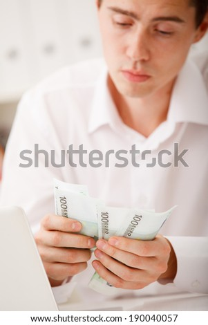 man counting money in office - stock photo
