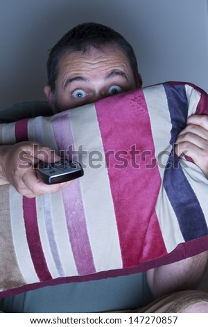 man covering face with a cushion watching tv - stock photo
