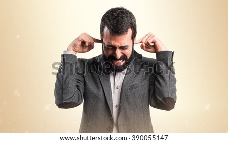 Man covering his ears over ocher background - stock photo