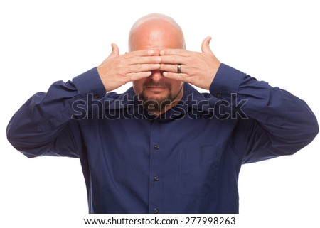 Man covering his eyes to see no evil. Portrait of bald, handsome young man isolated on white background.  - stock photo