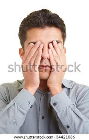 Man covering his eyes with his hands - stock photo