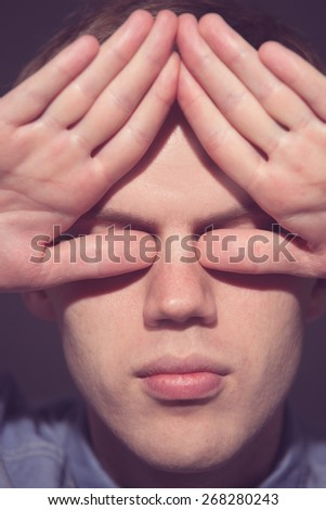 man covering his face with his both hands. old film toned - stock photo