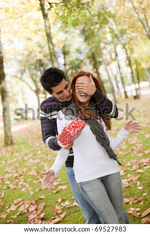 man covering the eyes to her girlfriend giving her a present (selective focus with shallow DOF) - stock photo