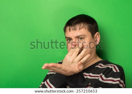 Man covers his nose due to a bad smell - stock photo