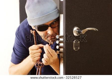Man cracks the door lock - stock photo