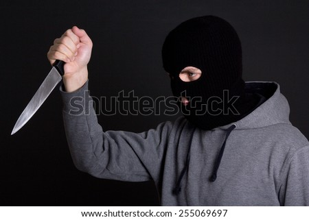 man criminal in black mask with knife over grey background - stock photo