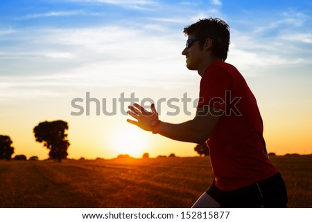 Man cross running and exercising on beautiful golden summer sunset background on countryside field. Male athlete fitness sportsman training. copy space. - stock photo