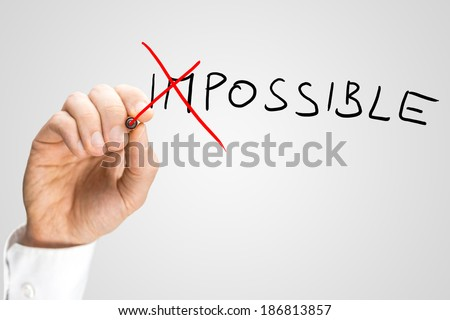 Man crossing through the Im in the handwritten word Impossible on a virtual screen with a red marker pen in a concept of opposites for Impossible - Possible. - stock photo