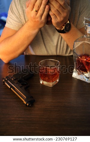 Man crying with gun and alcohol - stock photo