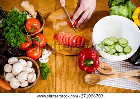 Man cuts fresh spring vegetables on the kitchen table, closeup. Preparing homemade food, home kitchen interior. - stock photo