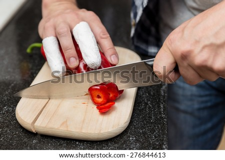 Man cuts with injured fingers red peppers - stock photo
