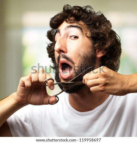 Man Cutting Beard against an abstract background - stock photo