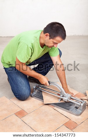 Man cutting floor tiles with manual cutter device - stock photo