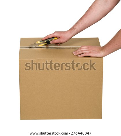 Man cutting tape on cardboard box - stock photo