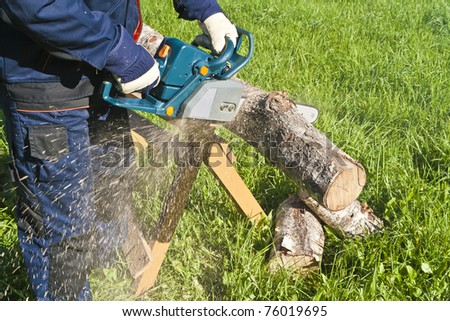Man cutting the log of wood with chainsaw - stock photo