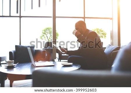 Man dealer is studying via touch pad securities before their purchase during coffee break in cafe. Male intelligent manager is drinking tea and reading something on digital tablet during rest in bar - stock photo