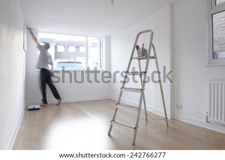 man decorating a room with ladder and paint pot in foreground - stock photo