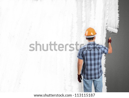 man decorating or painting house with a paint brush - stock photo