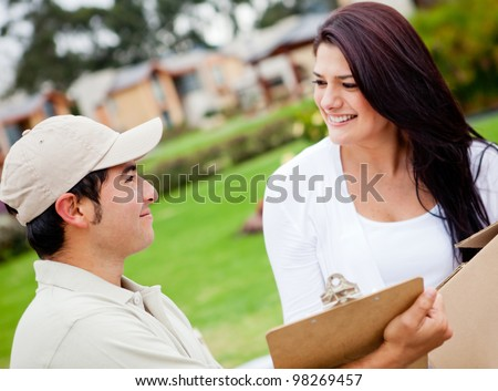 Man delivering a package and asking for signature - stock photo