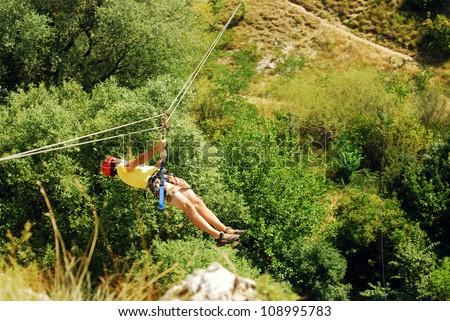 man descending on a zip-line (flying fox) - stock photo