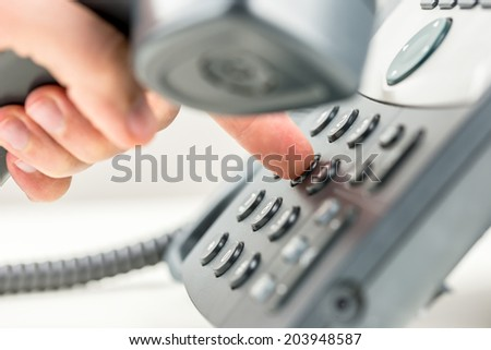 Man dialing out on a telephone holding the receiver in his hand and pressing the number on the keypad with his finger, close up view conceptual of communication. - stock photo