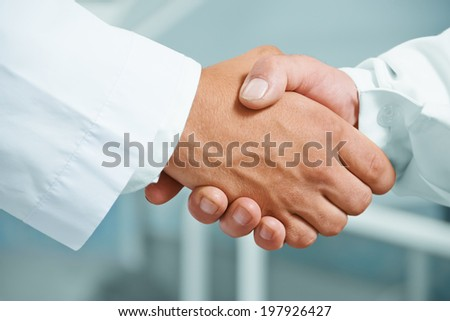 Man doctor shakes hand with another doctor in hospital, concept of teamwork - stock photo
